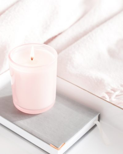 candle on book on tray on bed