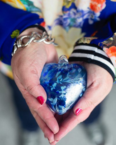 hands holding blue glass heart