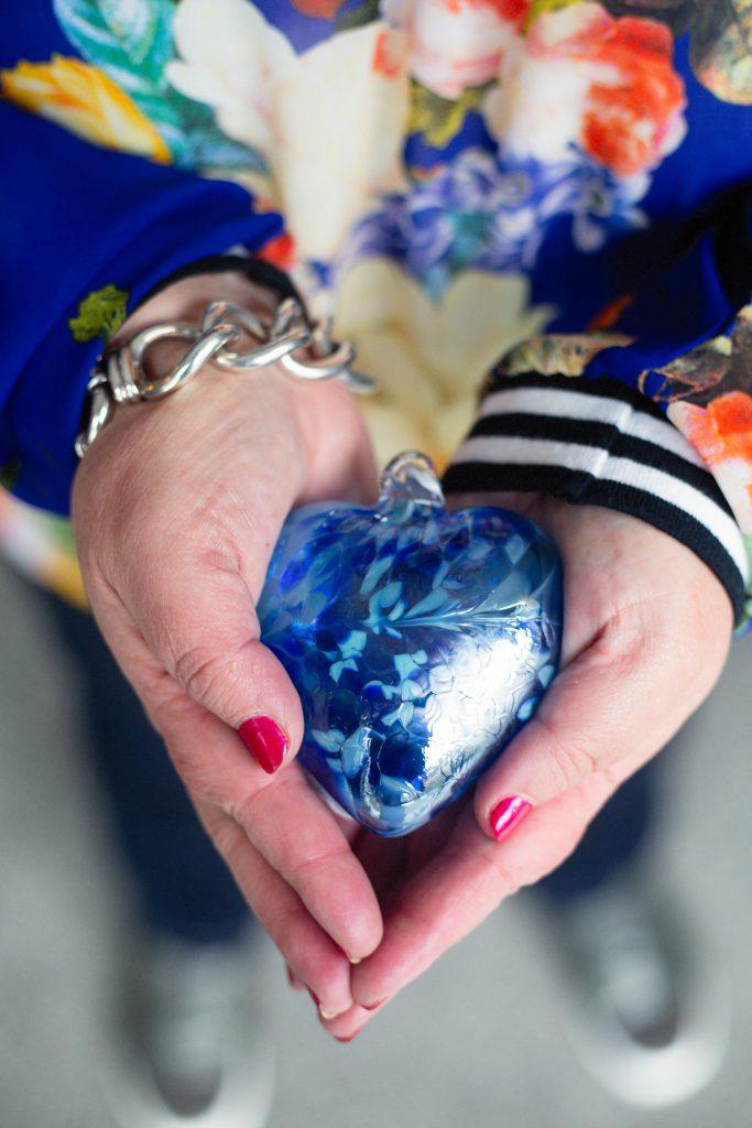 hands holding blue glass heart