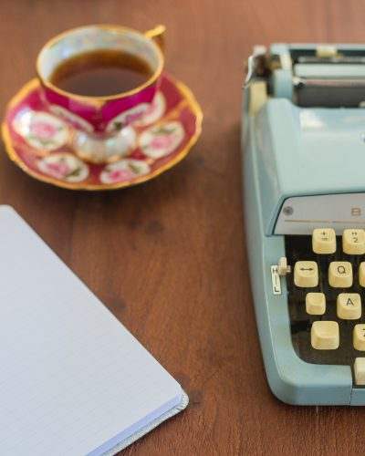 table with teacup typewriter and lined notebook with blank page