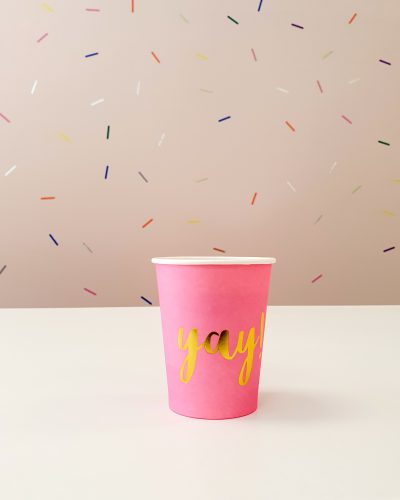 pink cup yay with sprinkles on a background wall