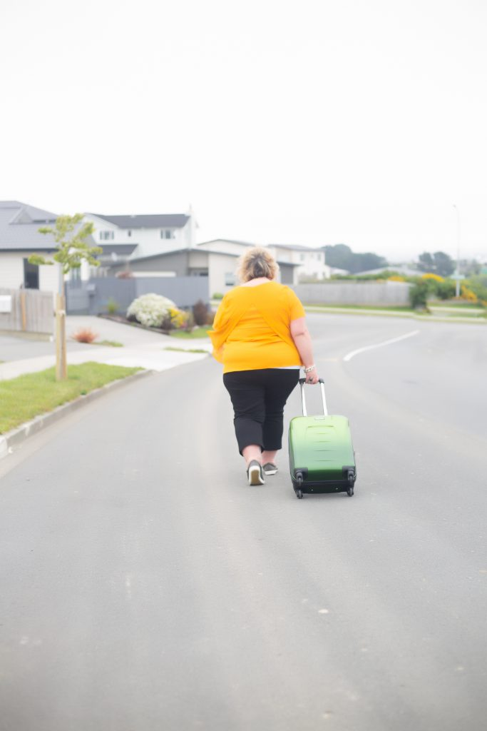 woman walking down road with a suitcase