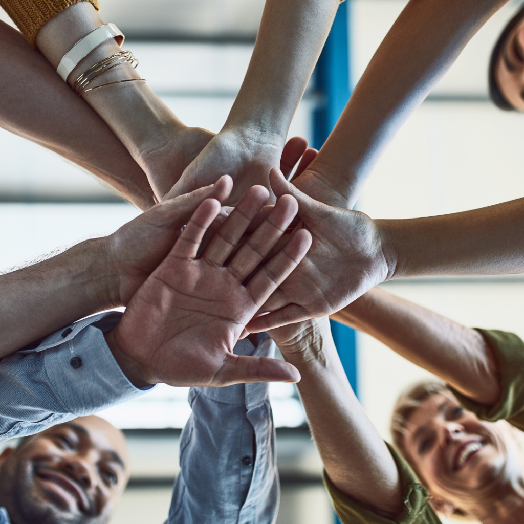 group of hands on top of each other meeting in the middle